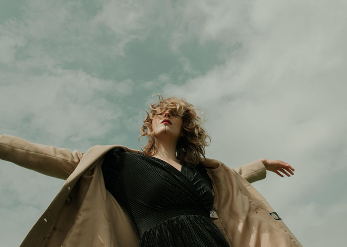 Low angle portrait of woman standing against cloudy sky