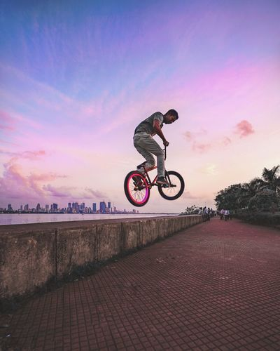Man Performing Stunt On Bicycle Against Sky During Sunset