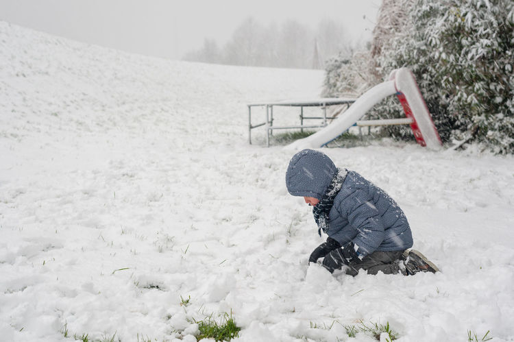 an boy in snow Winter Cold Temperature Snow One Person Warm Clothing Leisure Activity Nature Day Real People Full Length Childhood Lifestyles Child Land Men Boys Males  Field Outdoors Innocence Extreme Weather Hood - Clothing