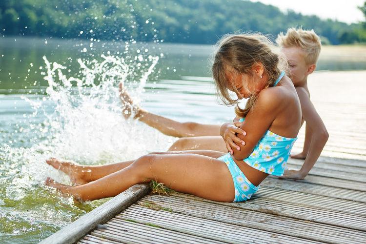 Siblings splashing water while sitting on pier over lake