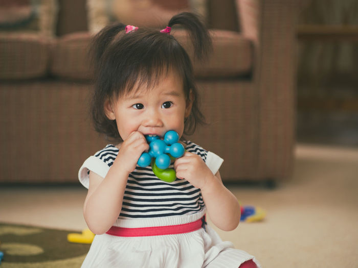Cute girl biting toy while sitting at home
