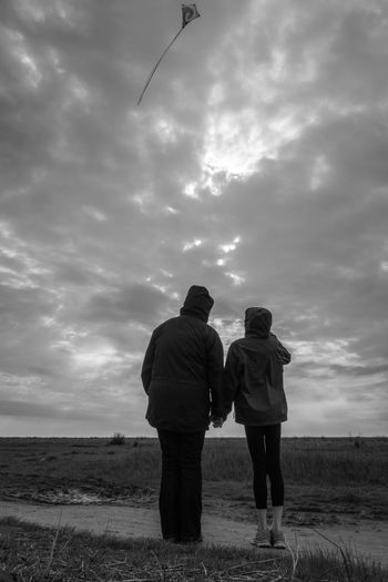 Couple standing on land against cloudy sky