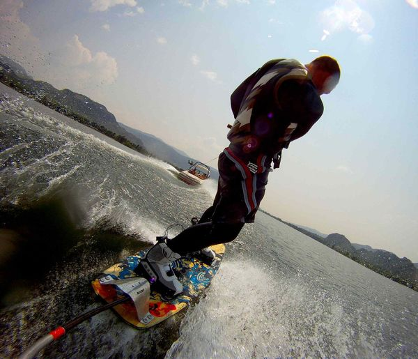 Low angle view of man wakeboarding in sea against sky on sunny day