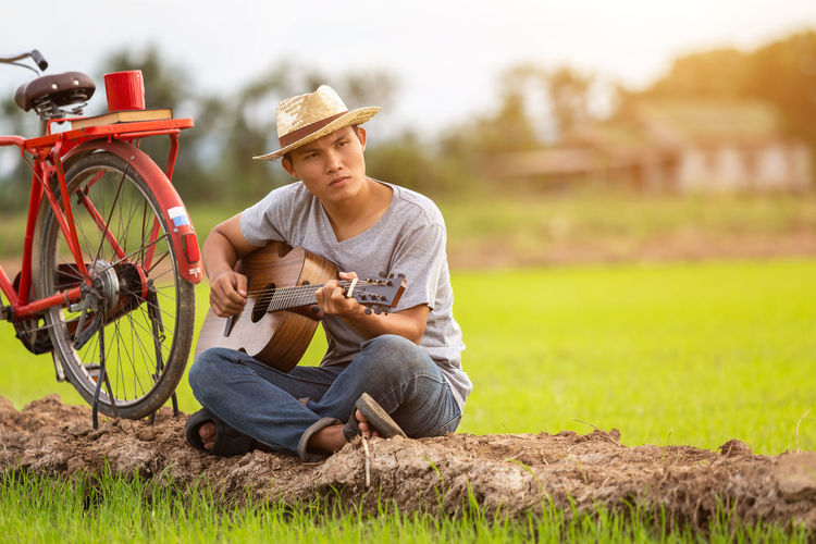 Man sitting on bicycle in field