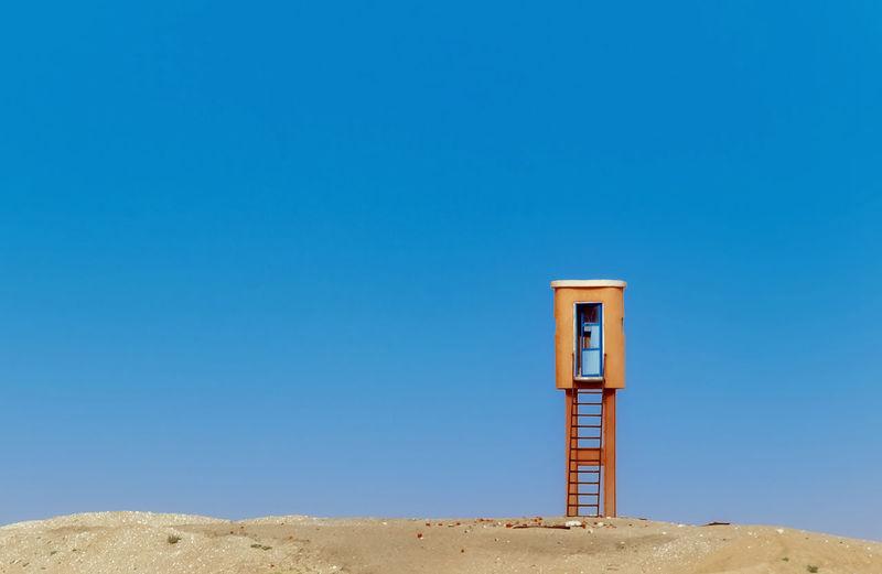 Lifeguard hut at beach against clear blue sky