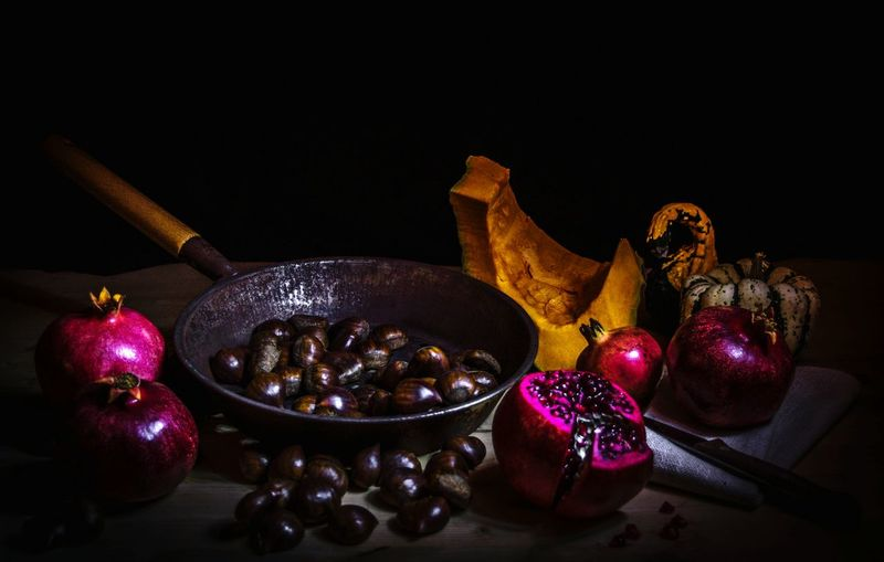 Roasted Chestnuts With Pomegranates And Pumpkins Against Black Background