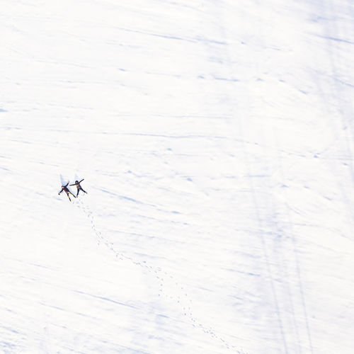 Aerial View Of Friends Lying On Snow Covered Field
