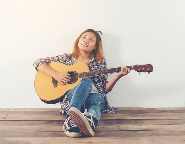 Smiling young woman playing guitar while sitting against white wall