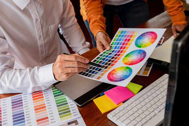 Midsection of creative business people discussing over color swatch at desk in office