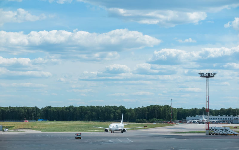 Runway and aircraft at the airport Cloud - Sky Sky Transportation Mode Of Transportation Road Car Motor Vehicle Land Vehicle Street Nature No People Tree Day Air Vehicle Airplane Airport Outdoors Plant Travel City