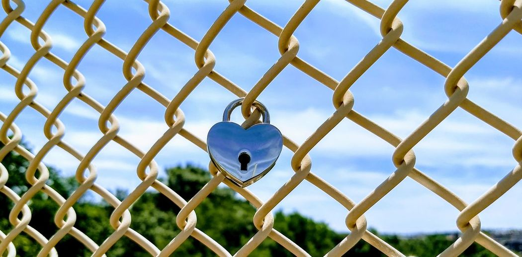 Close-up of padlock on chainlink fence against sky