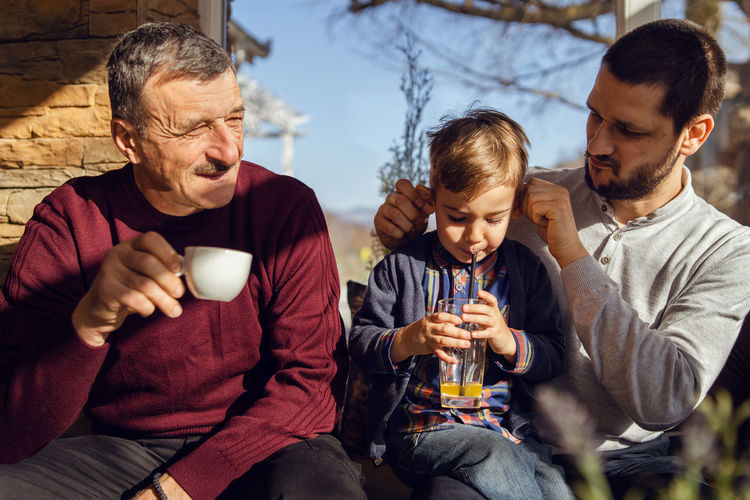 Father looking at son while sitting with grandfather at home