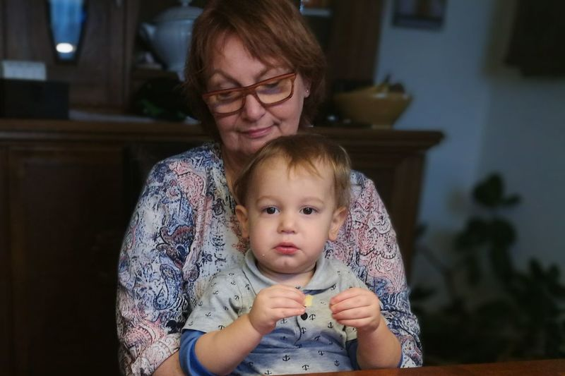 Senior Woman Sitting With Grandson At Home