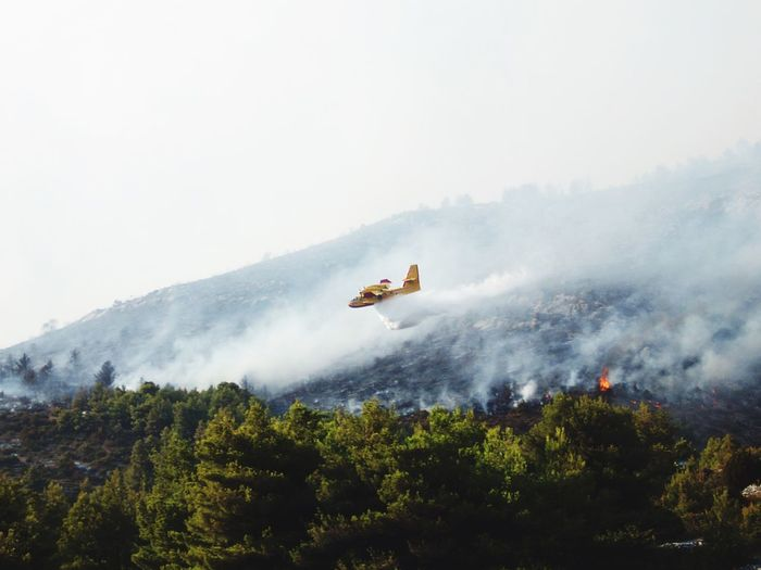 Smoke emoting from aircraft over mountain