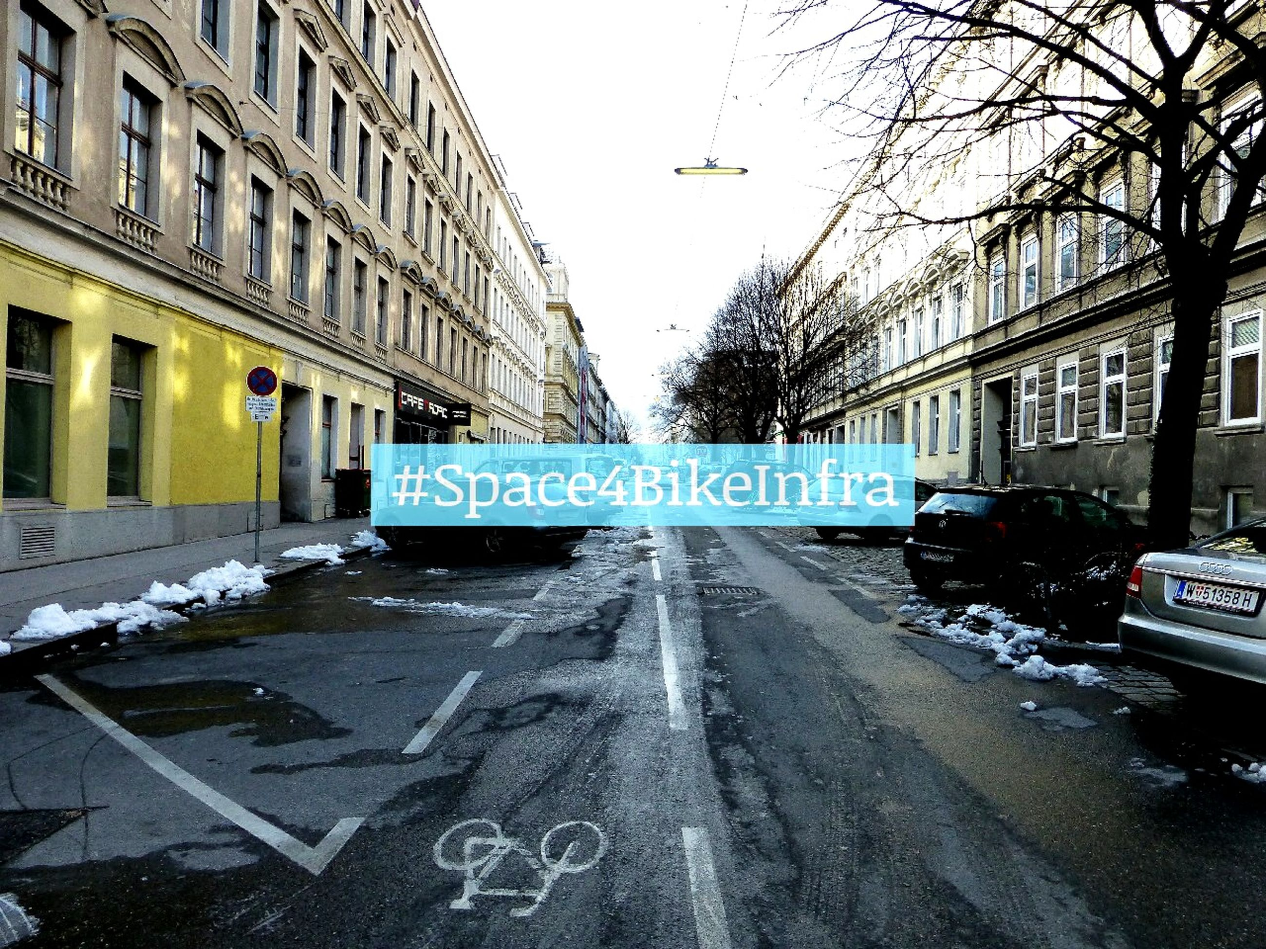 architecture, building exterior, built structure, transportation, street, city, car, road, snow, winter, bare tree, season, clear sky, cold temperature, text, road sign, land vehicle, mode of transport, city street, building