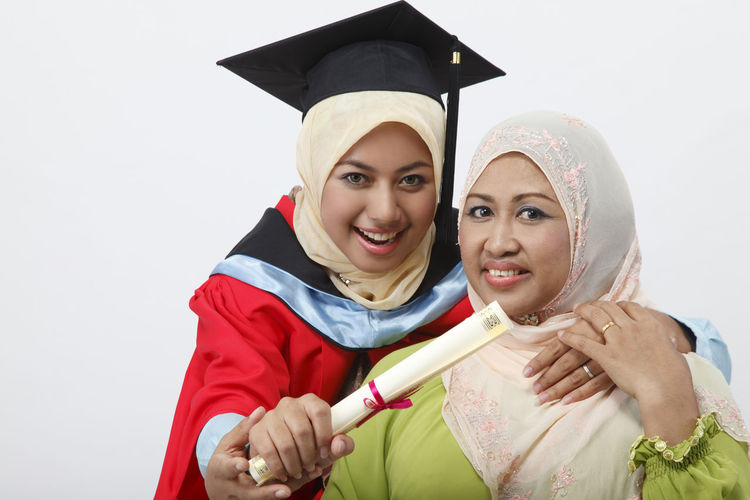 mother and daughter wearing graduation gown Achievement Graduation Happiness Hugging Isolated Mother & Daughter Muslimah Proud Mommy Beautiful Woman Certificate Education Graduation Gown Headwear Malay Ethnicity Mortarboard Portrait Scarf Smiling Studio Shot Success Toothy Smile Tudung Two People University Student White Background