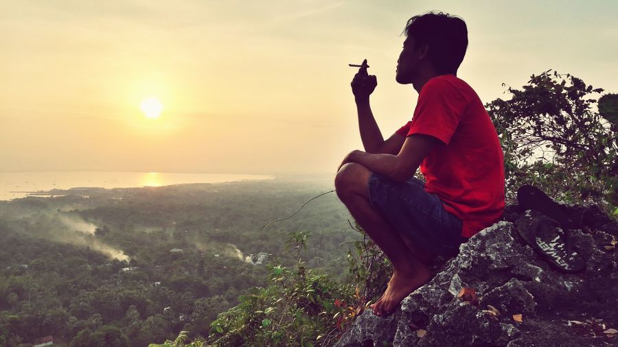 Side view of man smoking cigarette while sitting on mountain
