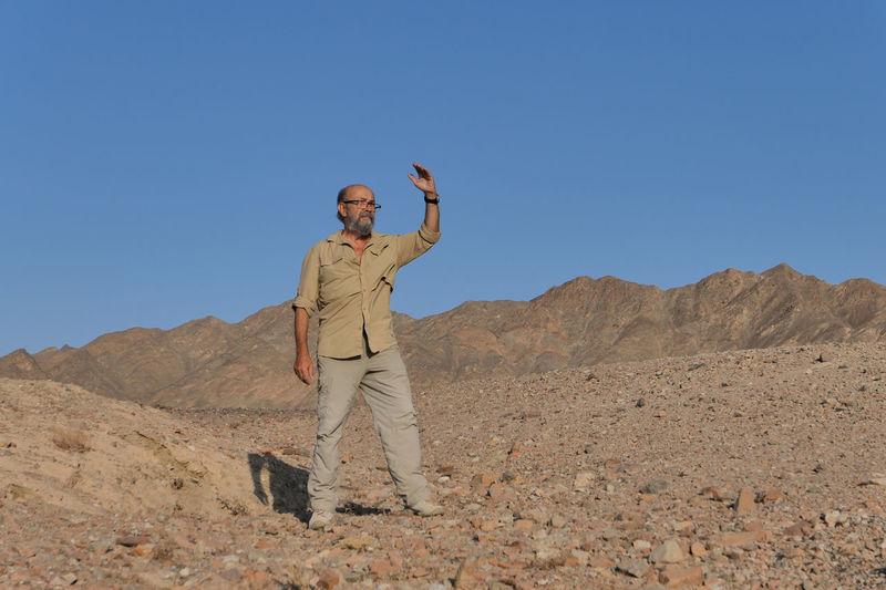 Full length of man standing on desert against clear sky