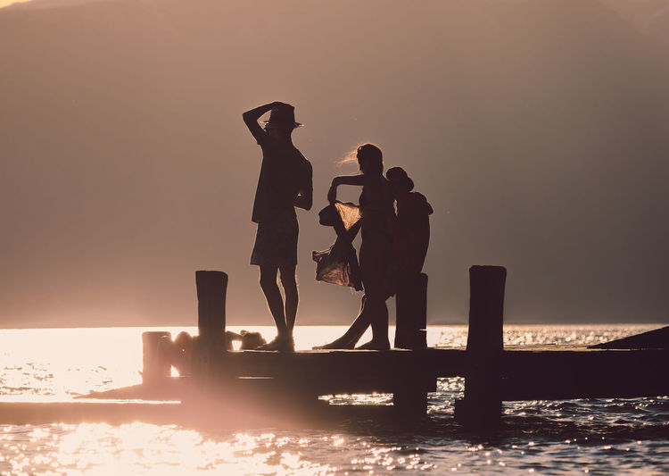 Silhouette people standing by sea against sky during sunset