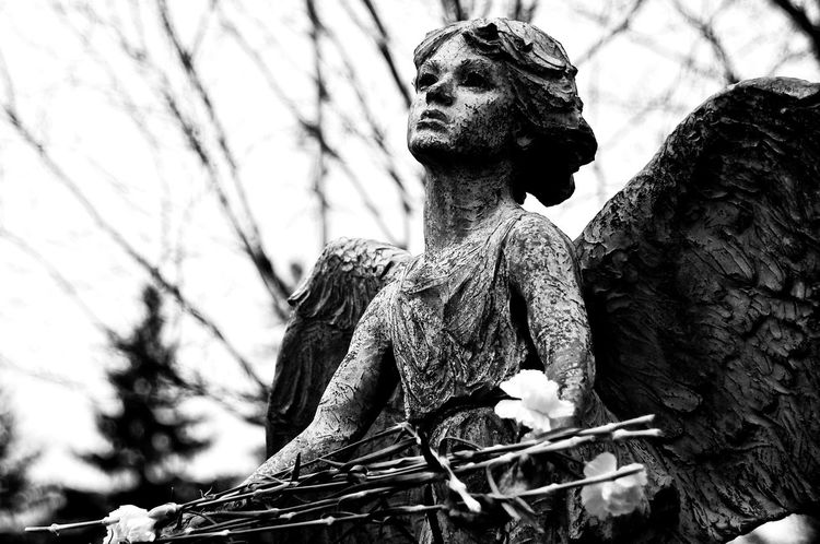 Angel of Hope in Monochrome. A tribute and memorial to loved ones lost, especially the children. On a chilly Spring morning, she holds flowers carefully laid in remembrance. B&W seems the most fitting format for this beautiful Angel of Hope. Angel B&w Photography Close-up Focus On Foreground Hope Human Representation Remembrance Sculpture