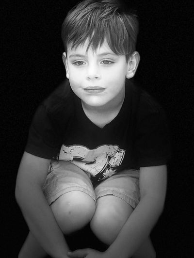 Portrait of boy holding camera over black background