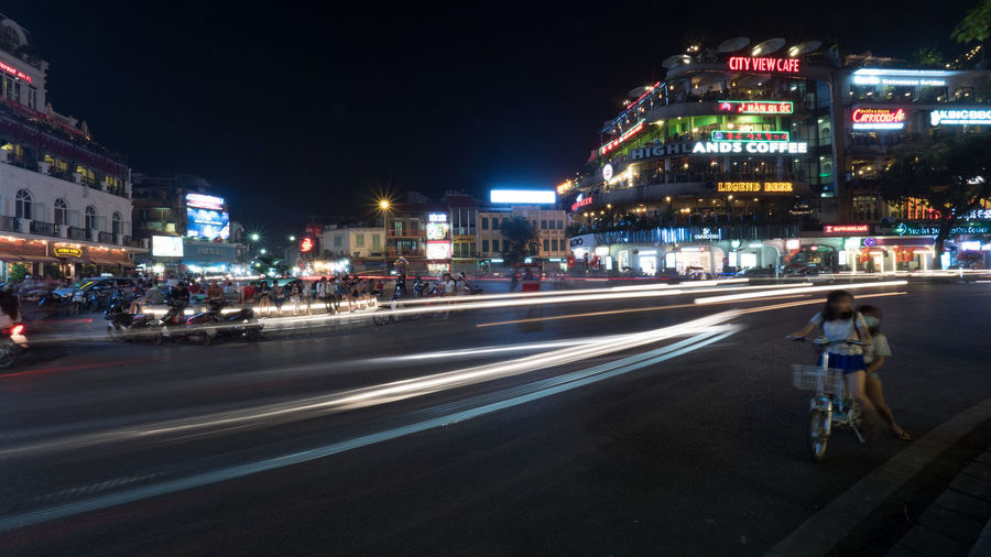 HANOI, VIETNAM - OCTOBER 27, 2015: Night city with lighted trails of moving transport on the road and buildings with illuminated banners ASIA Banner Car City City Life City Street Hanoi Horizontal Illuminated Motion Motorbike Night People Person Road Road Speed Traffic Transportation Urban Vietnam