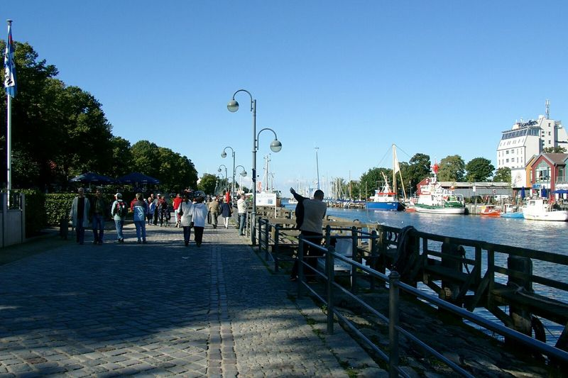 People Walking On Footpath By River Against Clear Blue Sky