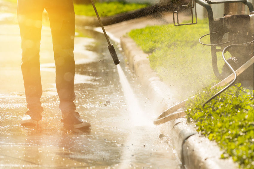 High pressure deep cleaning.Worker cleaning driveway with gasoline high pressure washer with rim light effect,professional cleaning services. Sunlight Worker Cleaning Services Day Dirty Driveway Gasoline Pump High Pressure Cleaner Motion One Person Professional Rim Light Splashing Spraying Water Wet