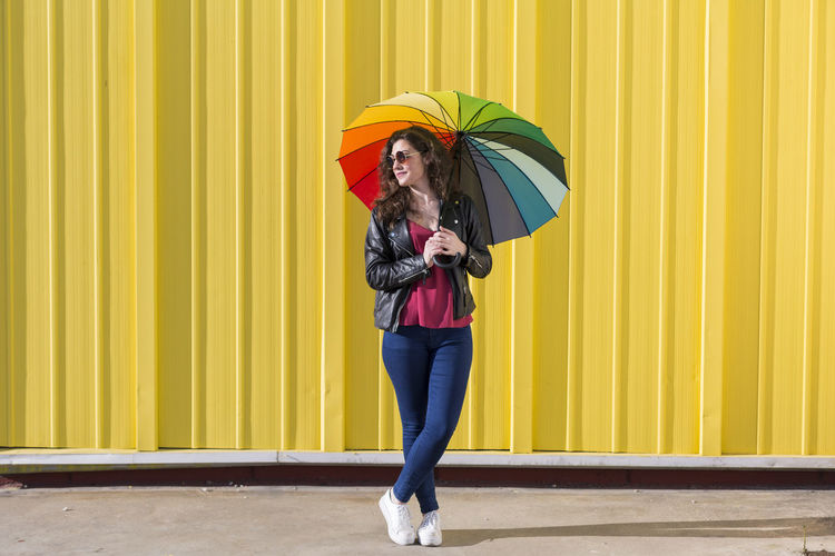 Young beautiful woman having fun with a colorful umbrella over yellow background. Happy. Lifestyle. Umbrella Woman Young Colorful Happy Smiling Lifestyles Cheerful Summer Spring Yellow Background Joy Fashion Sunglasses Street Casual Clothing Caucasian City Stylish Cool Trendy Enjoy Outdoors Holding Teenager Lady Attractive Jacket Jeans Jumping Positive Emotions Brown Hair Multicolored Gorgeous Laughing Makeup Playing Copy Space Concept Lifestyle Millennial Portrait Walking Model Beautiful Sunny Sun Sunset