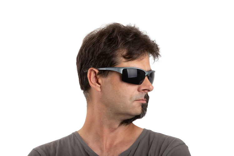 Portrait of man wearing sunglasses against white background