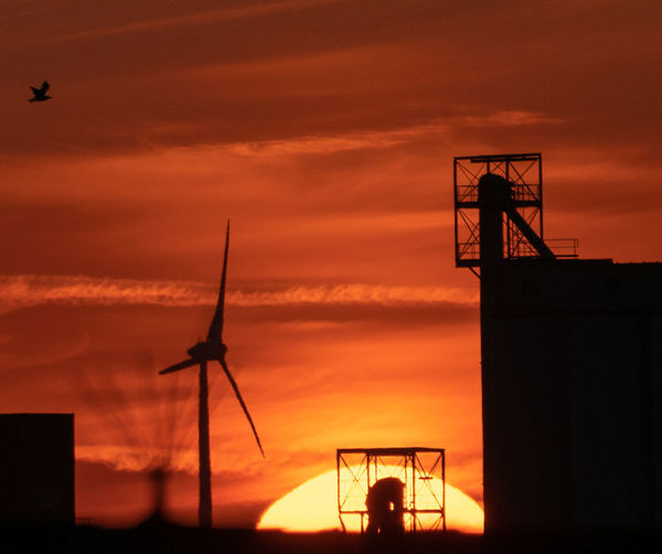 Low angle view of silhouette windmills against sky during sunset