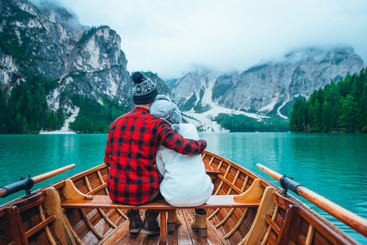 Rear view of man sitting on boat in lake against mountains