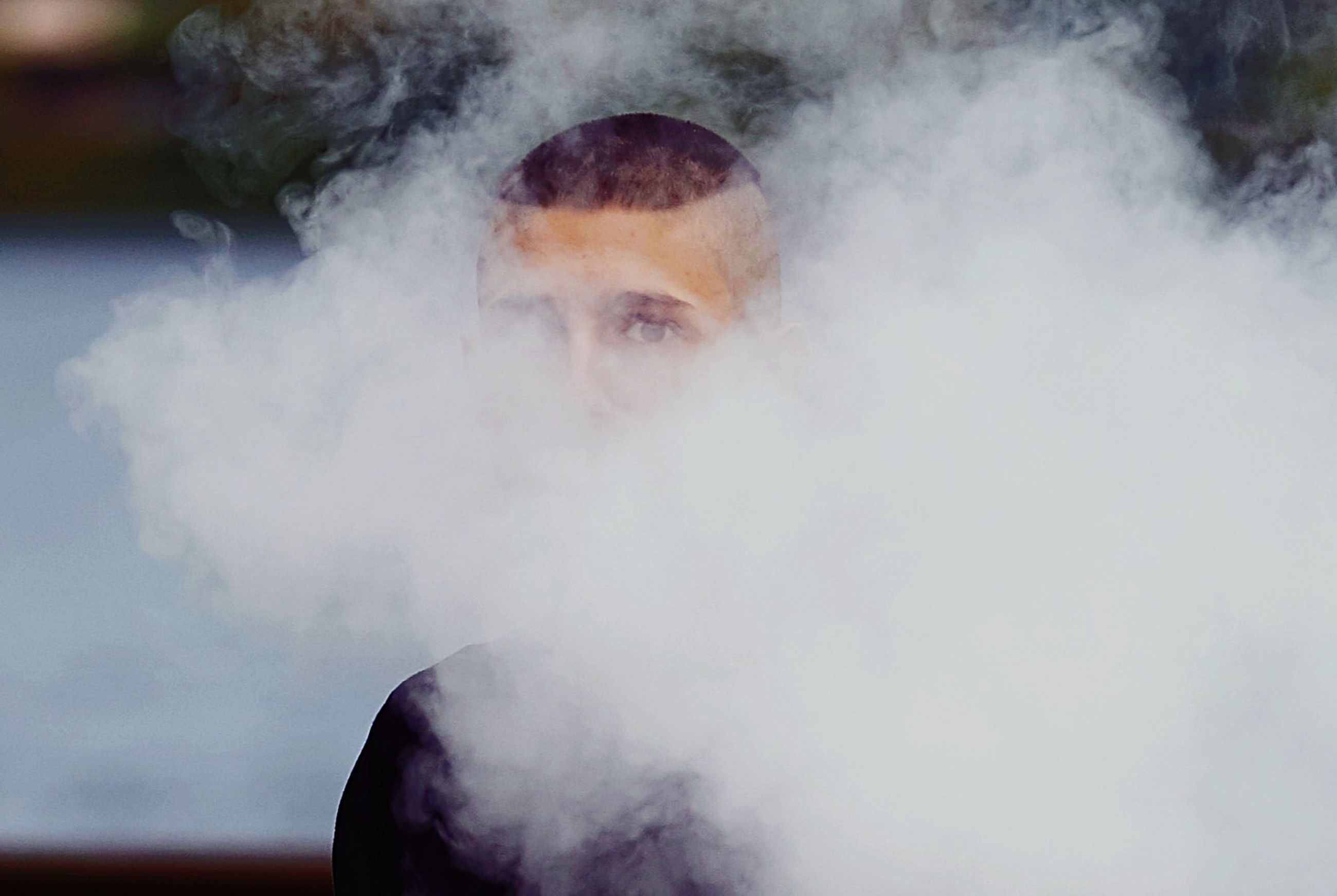 smoke - physical structure, one person, portrait, headshot, real people, front view, looking at camera, warning sign, lifestyles, smoking issues, leisure activity, young adult, sign, smoking - activity, bad habit, activity, pollution, obscured face