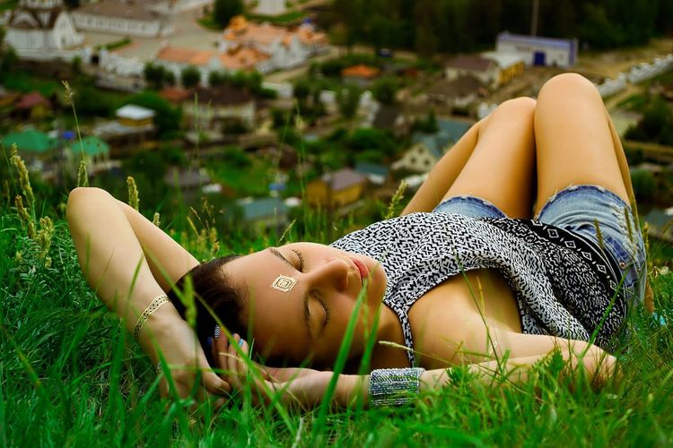 Close-up of woman lying on grass