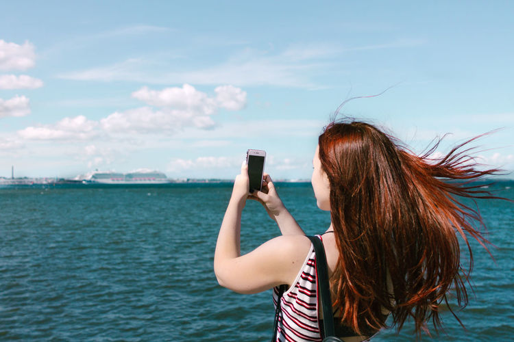 Woman Photographing With Mobile Phone By Sea Against Sky