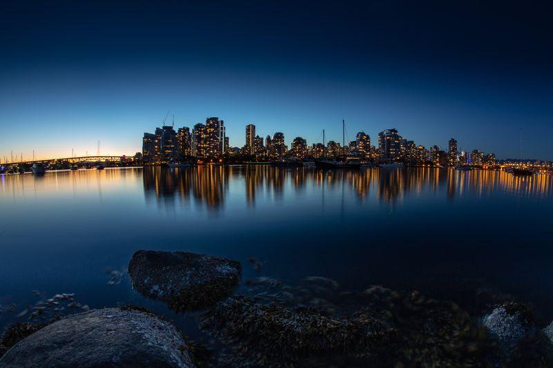 City Buildings By Sea Against Clear Blue Sky