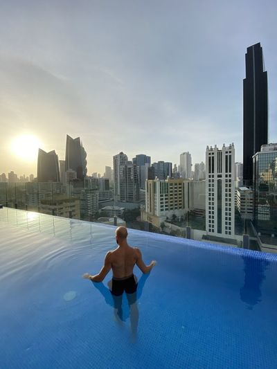 Full length of man in swimming pool against buildings in city