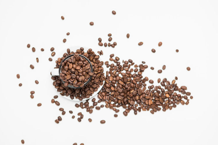 Top View of Coffee beans in a White Coffee cups on White Background Food And Drink White Background Studio Shot Indoors  Still Life Freshness Coffee - Drink Coffee Large Group Of Objects Food Roasted Coffee Bean High Angle View Brown No People Close-up Seed Directly Above Refreshment Drink Raw Food Caffeine