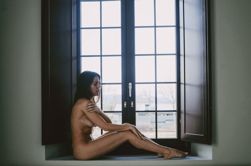 Side view of sensuous naked female model sitting on window sill