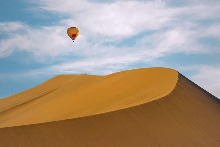 Low Angle View Of Hot Air Balloons Over Desert Against Sky