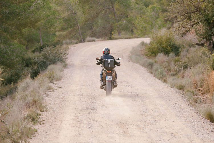 Woman riding motorcycle on dirt road