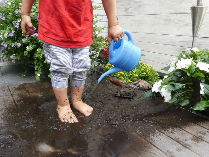 Low Section Of Child Standing On Deck With In Mud
