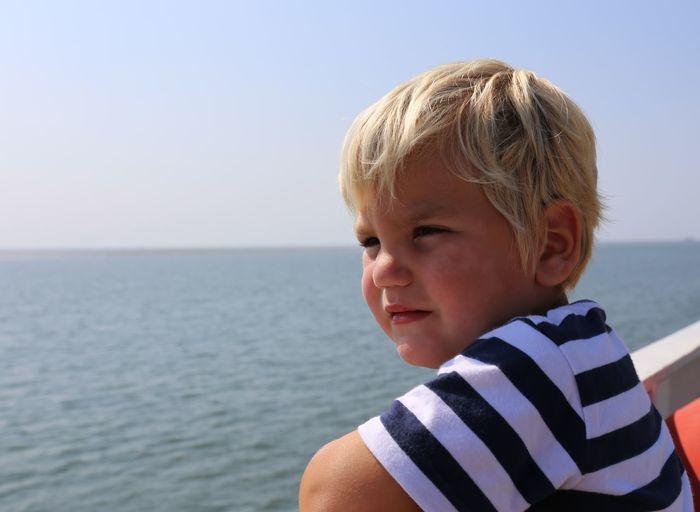 Portrait of boy against sea against sky