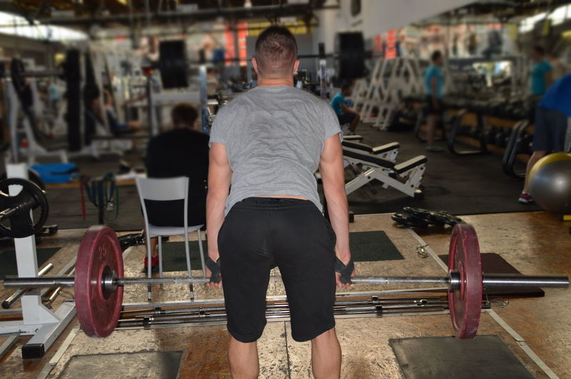 Rear View Of Mid Adult Man Lifting Weights In Gym