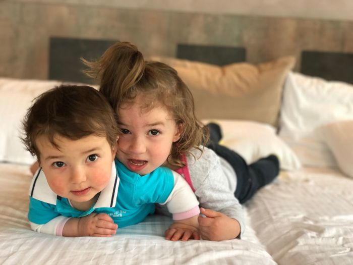 Portrait Of Cute Siblings Playing On Bed