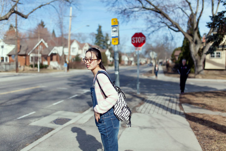 Side view of woman with backpack looking away while standing on sidewalk