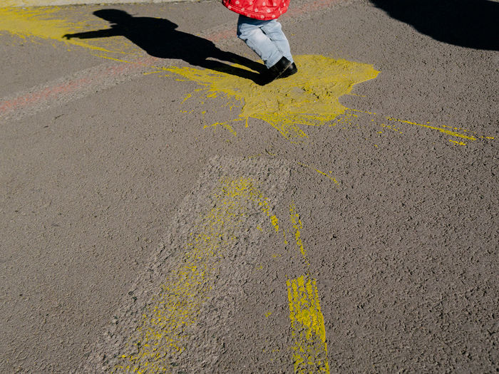 Low section of girl walking on road