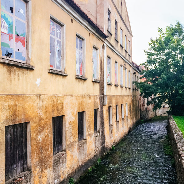 Aleksupite river winding through town, Kuldiga. Latvia Abandoned Alley Architecture Building Building Exterior Built Structure Deterioration Exterior Façade House Kuldiga Latvia Leading Narrow Old Residential Building Residential Structure River Ruined Summer Summertime Town Village Wall Window