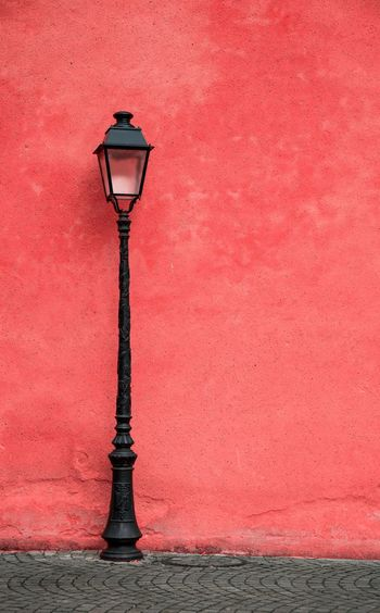 Close-up of street light against red wall