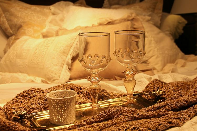 Empty Wineglass In Tray On Bed
